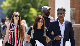 Former NFL players Ken Jenkins, right, and Clarence Vaughn III, center right, along with their wives, Amy Lewis, center, and Brooke Vaughn, left, carry tens of thousands of petitions demanding equal treatment for everyone involved in the settlement of concussion claims against the NFL, to the federal courthouse in Philadelphia, in this Friday, May 14, 2021, file photo. Lawyers for the NFL and retired players are due to file proposed changes to the $1 billion concussion settlement on Wednesday, Oct. 20, 2021, to remove race-norming in dementia testing, which made it more difficult for Black players to qualify for payments. (AP Photo/Matt Rourke, File)