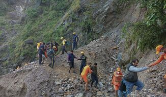 This photograph provided by India's National Disaster Response Force (NDRF) shows NDRF personnel rescuing civilians stranded following heavy rains at Chhara village near Nainital, Uttarakhand, Wednesday, Oct. 20, 2021. Nainital remained cut off from the rest of the state as roads leading to it were either blocked by landslides or washed away. ( National Disaster Response Force via AP)