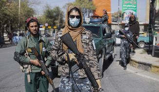 Taliban fighters stand guard during women's protest in Kabul, Afghanistan, Thursday, Oct. 21, 2021. (AP Photo/Ahmad Halabisaz)