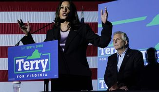 Vice President Kamala Harris, left, gestures while Democratic gubernatorial candidate, former Virginia Gov. Terry McAuliffe listens during a rally in Dumfries, Va., Thursday, Oct. 21, 2021. McAuliffe will face Republican Glenn Youngkin in the November election. (AP Photo/Steve Helber)