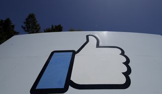 """This April 25, 2019, file photo shows the thumbs-up """"Like"""" logo on a sign at Facebook headquarters in Menlo Park, Calif. Amid a crush of bad publicity, governmental scrutiny and growing competition for its social media business, the company is hiring workers and making products to create the """"metaverse,"""" essentially a new computing platform and """"a new phase of interconnected virtual experiences using technologies like virtual and augmented reality,"""" according to company officials. (AP Photo/Jeff Chiu, File)  **FILE**"""