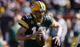 Green Bay Packers quarterback Aaron Rodgers runs with the ball during the first half of an NFL football game against the Chicago Bears Sunday, Oct. 17, 2021, in Chicago. (AP Photo/Nam Y. Huh)