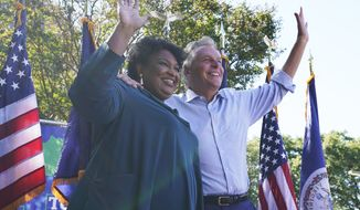 In this Oct. 17, 2021, photo, voting rights activist Stacey Abrams, left, waves to the crowd with Democratic gubernatorial candidate, former Virginia Gov. Terry McAuliffe, right, during a rally in Norfolk, Va. Polls have consistently shown about eight in 10 Black voters supporting McAuliffe against his Republican opponent, former business executive Glenn Youngkin, with Election Day on Nov. 2 now looming. (AP Photo/Steve Helber, File) **FILE**
