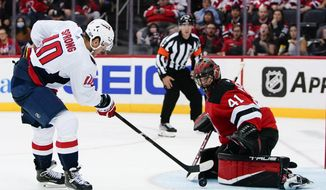 Washington Capitals' Daniel Sprong (10) shoots the puck past New Jersey Devils goaltender Scott Wedgewood (41) for a goal during the second period of an NHL hockey game Thursday, Oct. 21, 2021, in Newark, N.J. (AP Photo/Frank Franklin II)