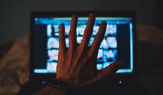 Hand over screen. Photo credit: Stenko Vlad/Shutterstock *FILE*