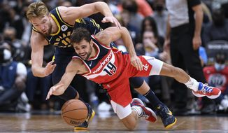Washington Wizards guard Raul Neto (19) and Indiana Pacers forward Domantas Sabonis (11) scramble for the ball during the second half of an NBA basketball game, Friday, Oct. 22, 2021, in Washington. The Wizards won 135-134 in overtime. (AP Photo/Nick Wass)