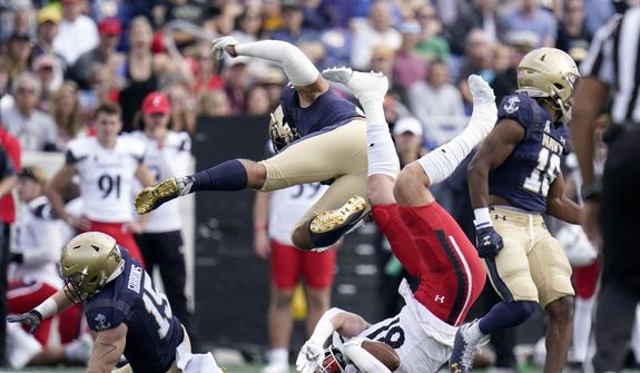 Navy linebacker Nicholas Straw, top, collides with Cincinnati tight end Josh Whyle, bottom, while going for a tackle of Whyle during the first half of an NCAA college football game, Saturday, Oct. 23, 2021, in Annapolis, Md. (AP Photo/Julio Cortez)