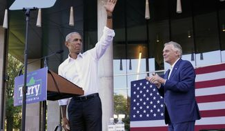 Former President Barack Obama, left, waves during a rally with Democratic gubernatorial candidate, former Virginia Gov. Terry McAuliffe, right, in Richmond, Va., Saturday, Oct. 23, 2021. McAuliffe will face Republican Glenn Youngkin in the November election. (AP Photo/Steve Helber)