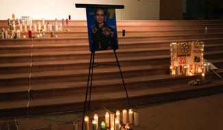 Candles are lit around a photo of cinematographer Halyna Hutchins during a candlelight vigil in Albuquerque, N.M., Saturday, Oct. 23, 2021. Hutchins died on Thursday after she wasfatally shot by actor Alec Baldwinwith a prop gun on a New Mexico film set. (AP Photo/Jae C. Hong)