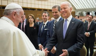 In this April 29, 2016, photo, Pope Francis shakes hands with then-Vice President Joe Biden as he takes part at a congress on the progress of regenerative medicine and its cultural impact, being held in the Pope Paul VI hall at the Vatican. (Pablo Martinez Monsivais/L'Osservatore Romano/Pool photo via AP) **FILE**