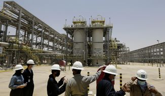 """In this June 28, 2021, file photo, Saudi Aramco engineers and journalists look at the Hawiyah Natural Gas Liquids Recovery Plant in Hawiyah, in the Eastern Province of Saudi Arabia. One of the world's largest oil producers, Saudi Arabia, announced on Saturday, Oct. 23,  it aims to reach """"net zero"""" greenhouse gas emissions by 2060, joining more than 100 countries in a global effort to try and curb man-made climate change. (AP Photo/Amr Nabil, File)  **FILE**"""