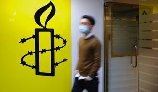 A man walks past the logo of the Amnesty International at its office in Hong Kong Monday, Oct. 25, 2021. Amnesty International said Monday it would close its two offices in Hong Kong this year, becoming the latest non-governmental organization to cease its operations amid a crackdown on political dissent in the city. (AP Photo/Vincent Yu)