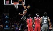 Washington Wizards' Montrezl Harrell (6) and Kentavious Caldwell-Pope (1) watch as Brooklyn Nets' Nic Claxton (33) dunks during the first half of an NBA basketball game Monday, Oct. 25, 2021, in New York. (AP Photo/Frank Franklin II)