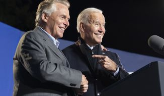 President Joe Biden, right, reacts after speaking at a rally for Democratic gubernatorial candidate, former Virginia Gov. Terry McAuliffe, Tuesday, Oct. 26, 2021, in Arlington, Va. McAuliffe will face Republican Glenn Youngkin in the November election. (AP Photo/Alex Brandon)
