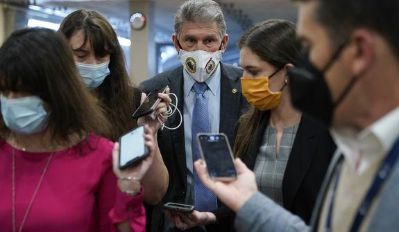 Sen. Joe Manchin, D-W.Va., center, speaks with reporters on Capitol Hill in Washington, Wednesday, Oct. 27, 2021. (AP Photo/Patrick Semansky)