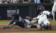 Atlanta Braves' Dansby Swanson scores past Houston Astros catcher Jason Castro on a sacrifice fly during the eighth inning of Game 1 in baseball's World Series between the Houston Astros and the Atlanta Braves Tuesday, Oct. 26, 2021, in Houston. (AP Photo/Sue Ogrocki)