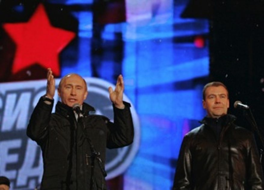 ** FILE ** Vladimir Putin (left) and his handpicked successor, Dmitry Medvedev, greet supporters in Moscow's Red Square during a concert to mark the presidential election in March 2008. (AP Photo/RIA-Novosti, Vladimir Rodionov, Presidential Press Service)