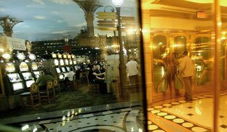 ** FILE ** Tourists play slot machines at the Paris hotel-casino in Las Vegas. (Associated Press)